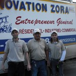 Salim Velji (centre) and two members of his renovation crew stand by the company white truck