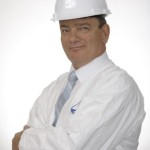Roger Tomassini, president of Tomassini Injection wearing a white jacket and a white hard hat. He is a specialist of foundation repair