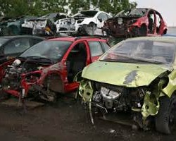 Auto scrap yard showing a red and a green cars that were in an accident